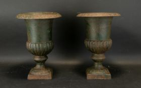 A Pair Of Cast Metal Urns Each raised on square base, each 13 inches in height, 9 inches diameter.