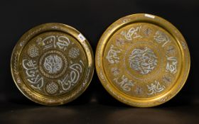 Two Antique Islamic Brass Chargers Each with inlaid silver script, diameters 18 and 16 inches.