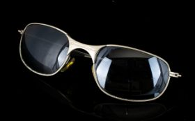 Oakley Sunglasses A pair of vintage Oakley sunglasses with steel frames with the Oakley insignia.