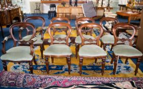 A Set of Eight Balloon Back Dining Chairs comprising two carvers and six dining chairs,