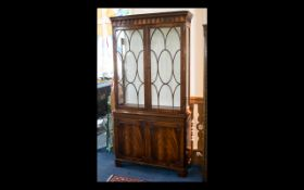 A Glazed Bookcase By Reprodux Comprising astral glazed two door cabinet with three integral glazed