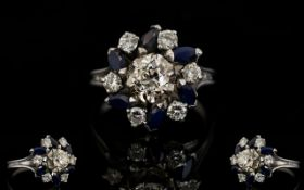 18ct White Gold Diamond And Sapphire Cluster Ring The central diamond surrounded by alternating