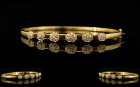 An 18ct Gold Diamond And Ruby Set Bangle Hinged yellow gold bangle set with five calibre cut rubies