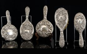 Embossed Silver Backed Vanity Items Five pieces in total, to include mirrors and brush two