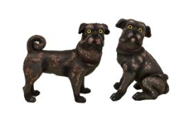A Pair Of Freestanding Resin Pug Figures Each with yellow glass eyes, one depicted in seated pose,