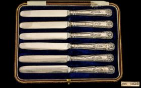 A Boxed Set of Six Ornate Silver Handle Butter Knives with Steel Blades.