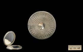 A Silver Compact Of circular form, mirror and sifter intact,