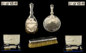 A Cased Vanity Set comprising a silver backed hand mirror, hair brush and clothes brush,
