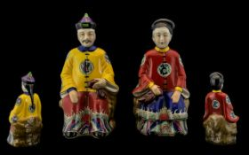 A Pair of Oriental Seated Figures depicting Emperor and Empress in bright coloured traditional
