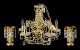 A Gilt Metal And Crystal Ceiling Pendant Five branch light fitting with gilt arts, cut glass column,