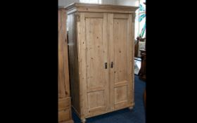A Good Quality Solid Pine Two Door Wardrobe with the two panelled doors opening to reveal storage
