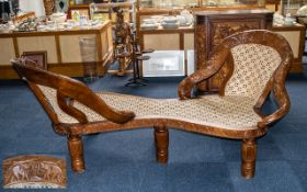 A Large Loving Chair of solid wooden construction with a rattan seat and back rest and carved arms.