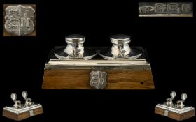 A Silver Arts And Crafts Dual Well Inkstand Of rectangular form, raised on golden oak base,