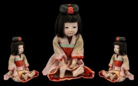 Vintage Japanese Ichimatsu Doll with original pink kimono with red sash, glass eyes and hair in bun.