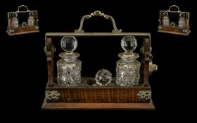 An Edwardian Three Bottle Miniature Tantalus golden oak with nickel plated strap work and handle.