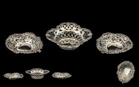 A Pair of Silver Pierced Bon Bon Dishes with embossed decoration. Hallmarked for Chester B- 1902.