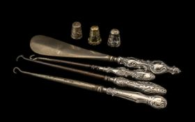 A Collection of Three Silver Handled Button Hooks, together with a silver handled shoe horn and