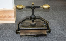 A Victorian Iron Book Press of typical square form, in black and enamelled cast iron.