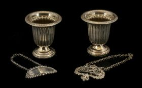 A Pair of Sterling Silver Salts in the form of footed urns of fluted form and with a weighted base.