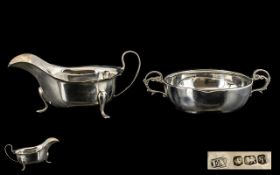 A Silver Twin Handled Porringer of Plain form with a molded edge and scroll handles.