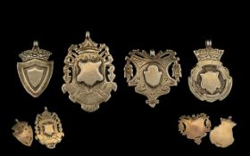A Collection of Four Silver Fobs / Medals featuring un engraved crests / shields.