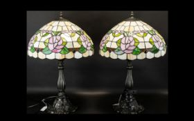 A Pair Of Reproduction Tiffany Style Table Lamps each raised on bronzed metal base with shaped