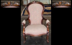 A Mahogany Victorian Style Spoon Back Arm Chair with carved back rest and front legs, a padded