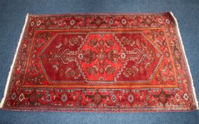 An Afghan Wool Rug with a red ground and geometric design. Measuring 4' 6 by 7 feet. Good condition.