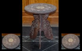 A Carved Indian Tripod Table with pierced leaf decorated support. The top with bone inlay and leaf