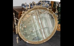 An Early 19thC Large Gesso Framed Wall Mirror with applied floral bow and garland pediment and
