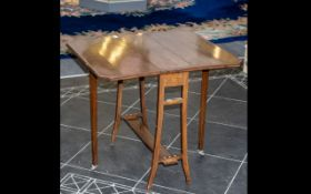 An Edwardian Mahogany Sutherland Drop Leaf Table with a satin wood edge and square splayed