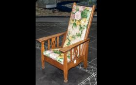 Child's Reclining Chair. Oak framed chair, with floral upholstery, raised on four legs. Height