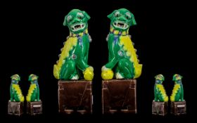 Late Qing Period Pair of Famille Verte Temple Foo Dogs - of typical form, seated on square aubergine