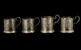 A Set of Four Antique Mogul/Indian Silvered Metal Embossed Tea Glass Holders decorated to the body