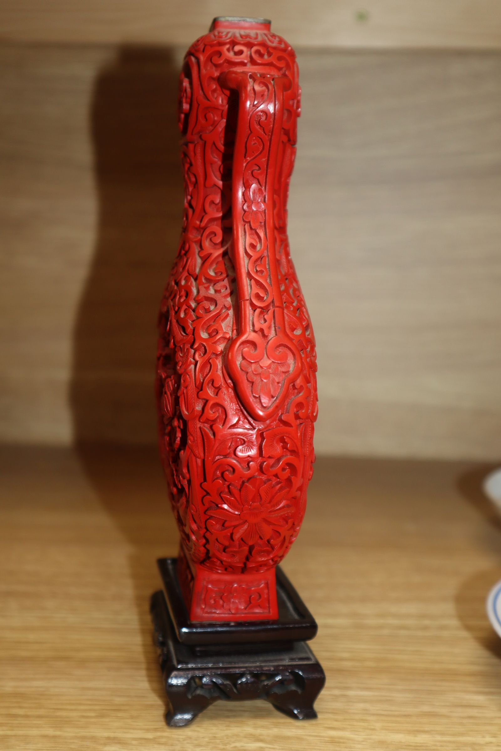 Lot 83 - A cinnabar lacquer vase on associated hardwood stand height 20.5cm excluding stand