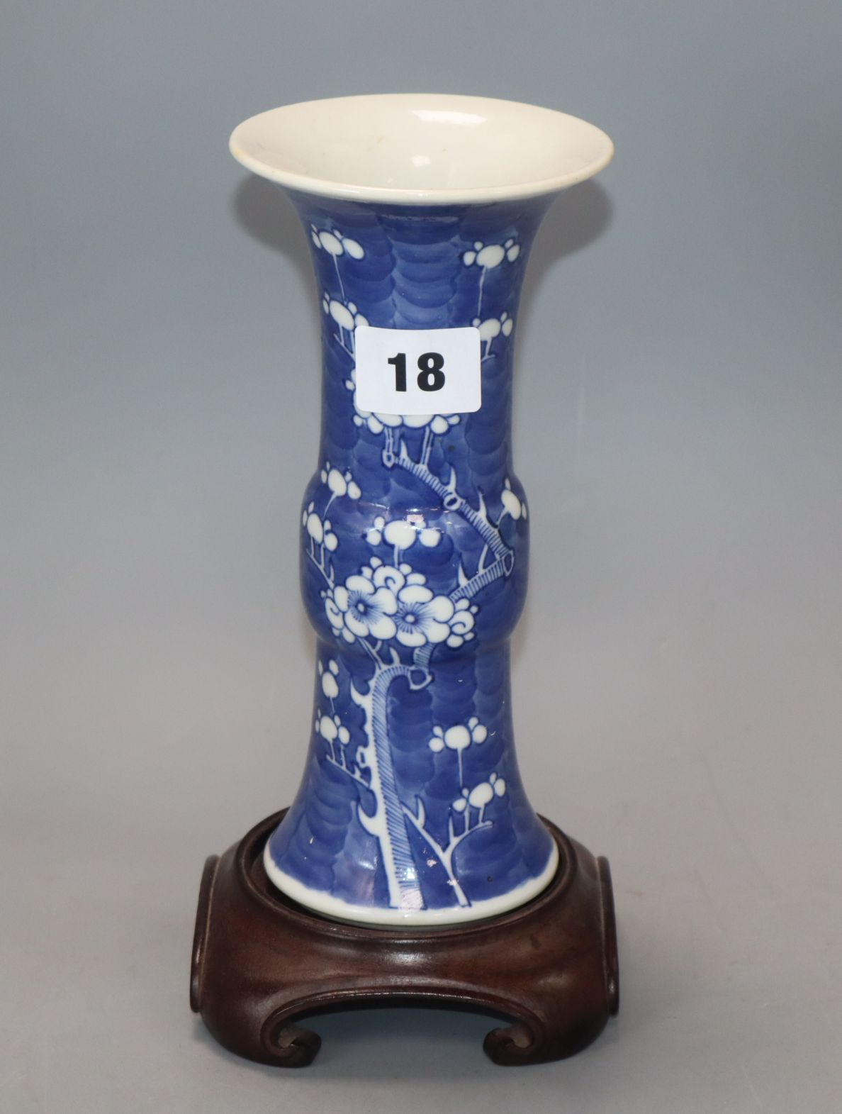 Lot 18 - A Chinese blue and white 'prunus' beaker vase, 19th century, wood stand height 20cm excluding