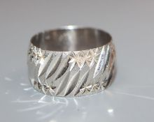 An 18ct white gold bright cut engraved modernist wedding band, size P/Q.