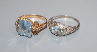 A 14k white metal and aquamarine ring and a 750 yellow metal and synthetic spinel? ring.