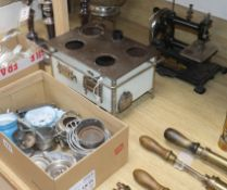 A child's tinplate cooking stove with accessories and a German-made child's sewing machine with gilt