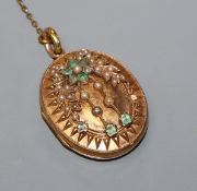 A Victorian yellow metal, emerald and seed pearl set oval locket, 35mm.