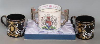 A pair of Wedgwood commemorative ware mugs and a Paragon china mug