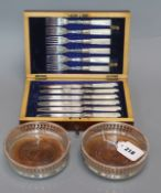 A cased set of mother of pearl handled fruit eaters and two coasters