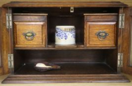 An oak smoker's cabinet with a cased meerschaum pipe
