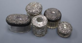 Five assorted early 20th century repousse silver mounted toilet jars, largest 8cm.
