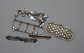 A paste set white metal buckle and three other paste set brooches, largest 63mm.