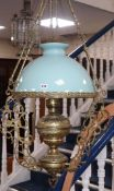 A brass hanging light and glass shade