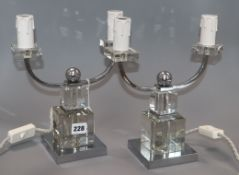 A pair of Art Deco style chromium and glass two-branch candelabra
