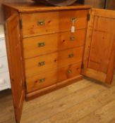 A pine cupboard with fitted campaign handle drawers W.92cm