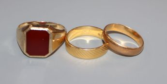 A 22ct yellow gold engraved wedding band, a similar plain band and a 9ct yellow gold signet ring