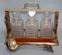 An Army and Navy three bottle tantalus and two serving spoons width 42cm